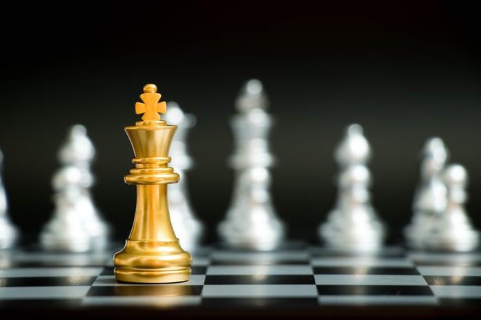 Une pièce d'échecs du roi d'or parmi des pièces d'argent, représentant un gagnant.
