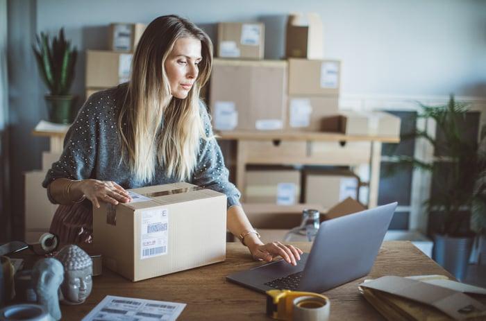 Une femme utilise son ordinateur portable alors qu'elle se prépare à envoyer une commande de son magasin.