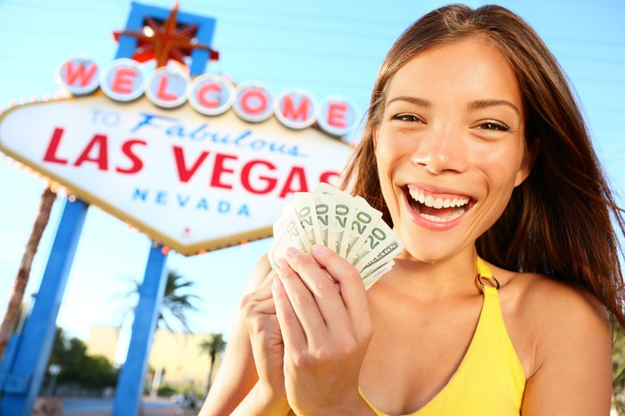 A woman holding a fan of 20-dollar bills in front of a Las Vegas sign.