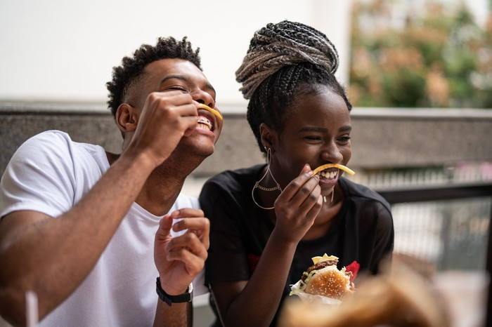 Two young people playing with their french fries in a fast-food restaurant.