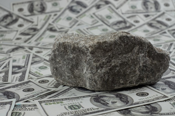 A rock sitting on piles of money.