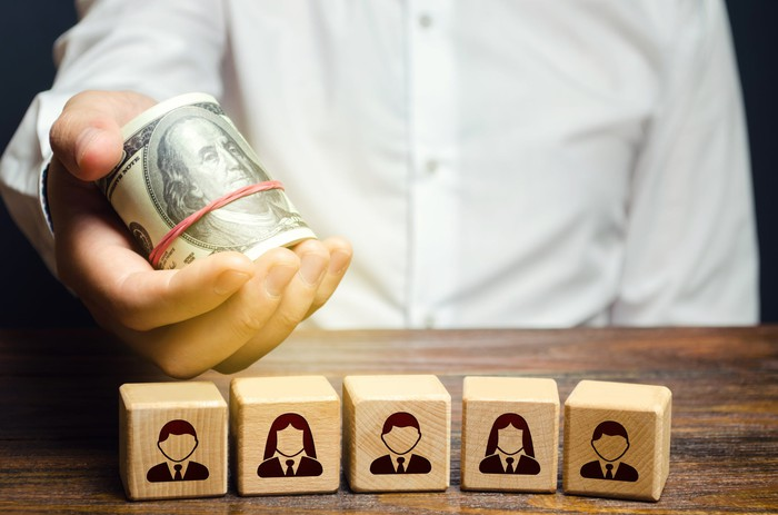 A man holds a roll of cash over blocks representing employees.