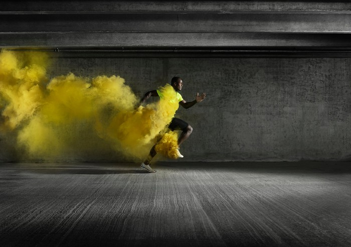 A runner sprinting with yellow smoke in his wake.