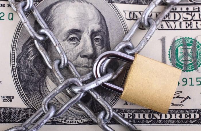 A padlock protecting a U.S. $100 bill.
