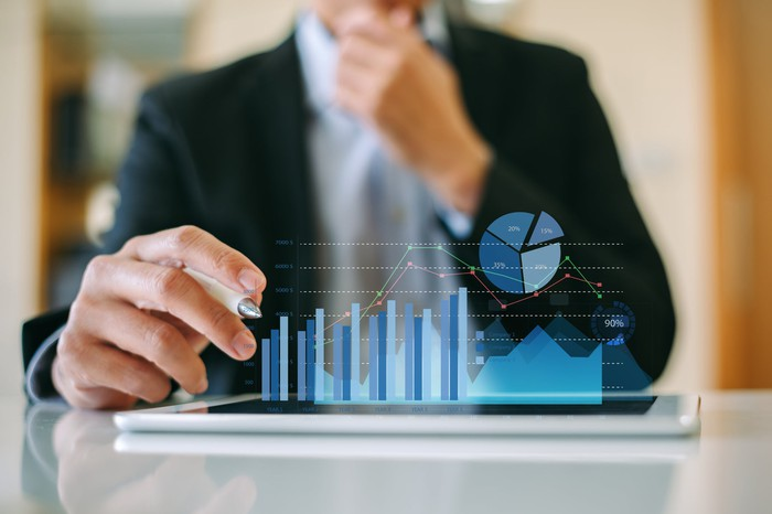 A man siting in front of a bar graph.