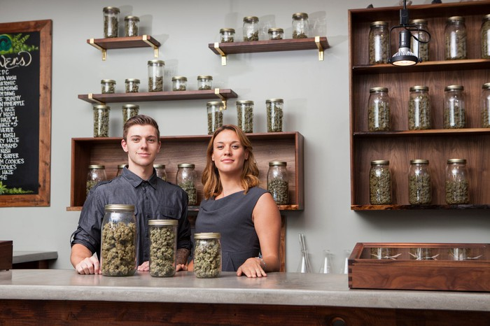 A pair of shopkeepers at a cannabis dispensary stand triumphantly in front of three jars filled with cannabis flower.