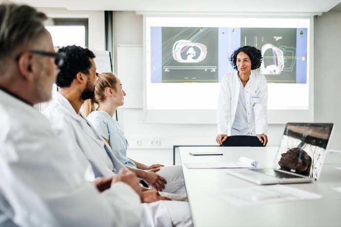 Two female and two male doctors in white coats sit around a table discussing data and medical scans.