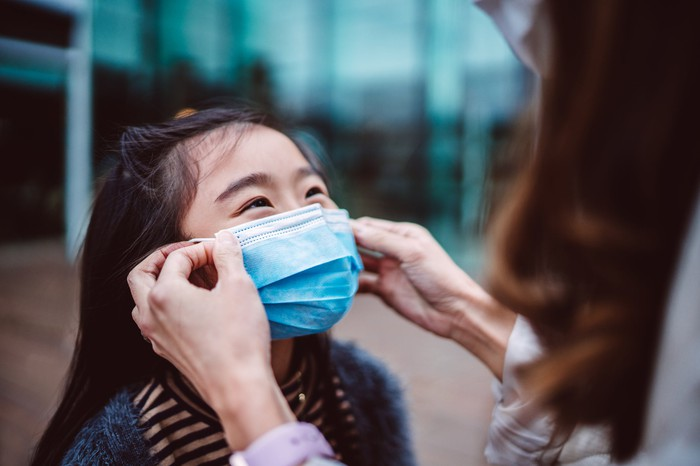 Adult woman places a blue surgical mask over a young girl's nose and mouth.