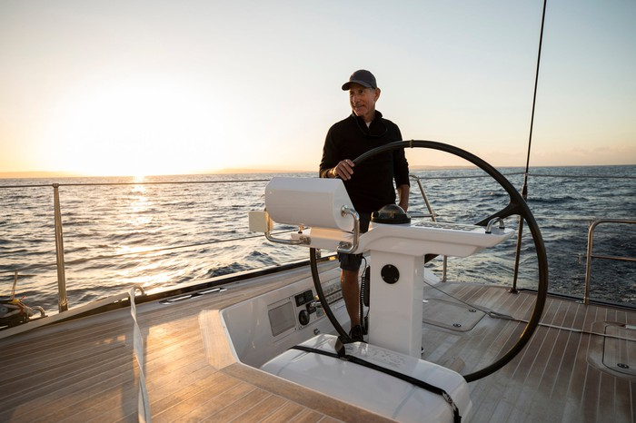 An older man at the steering wheel of a large boat.