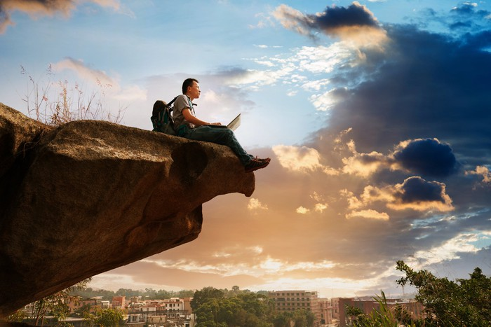 Man sitting on cliff edge  as he works on his laptop