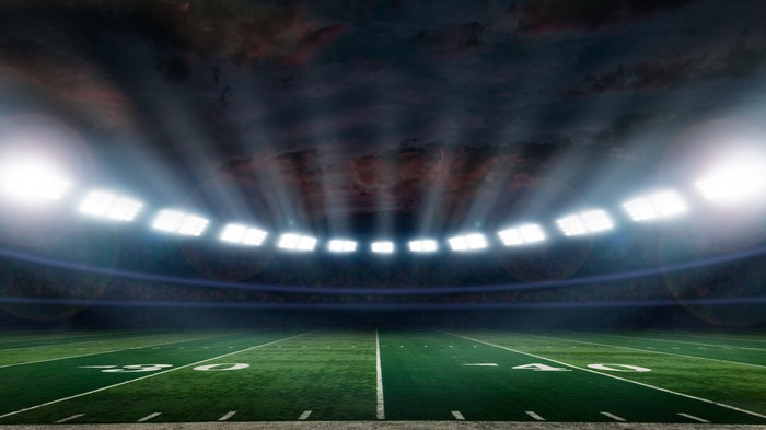 A football stadium with all lights on.