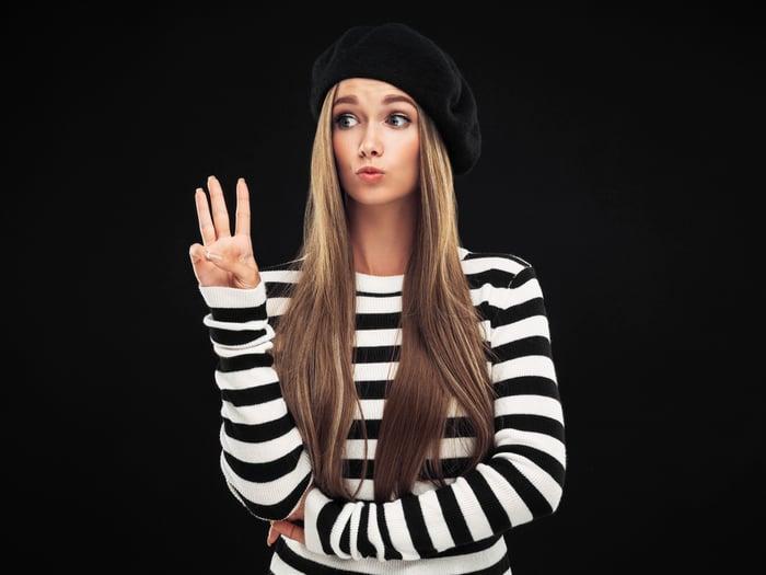 Une femme portant un béret noir tenant trois doigts.