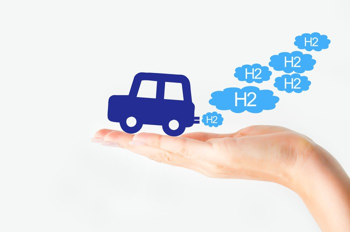 Cartoon fuel cell car on palm of hand putting out H2 bubbles as exhaust.