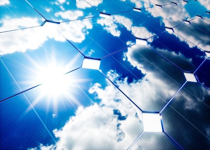 Un panneau solaire reflète le soleil dans un ciel partiellement nuageux.