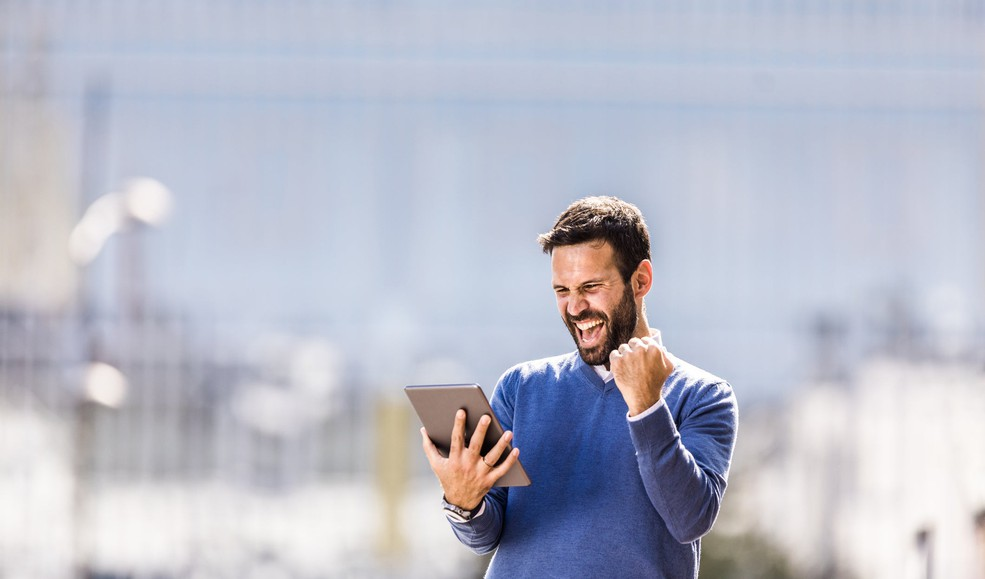 Man holding tablet and smiling in celebration_GettyImages-1043480214