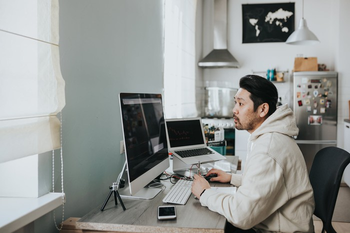 Man wearing a sweatshirt sits at a desk at home in front of a large monitor and laptop.