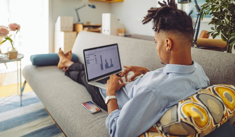 young man lounges on a long grey couch while working on his laptop