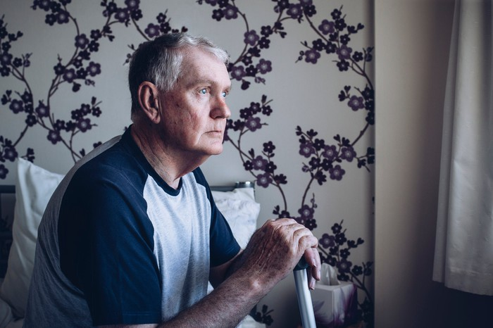 Older man in dark room sitting and clutching cane