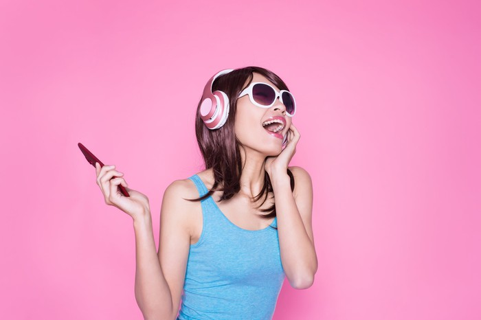 A woman holding a phone and wearing headphones.