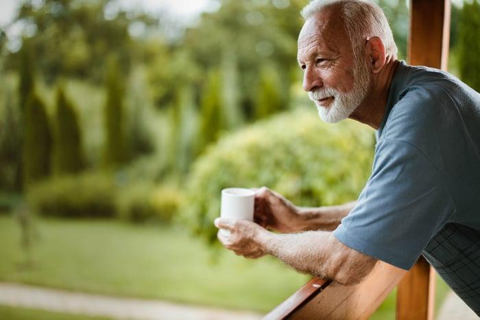 Older man holding mug while leaning over railing