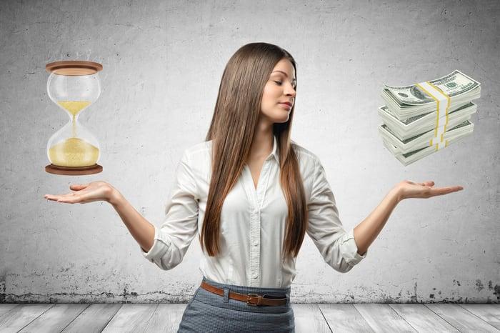 Femme tenant les deux paumes de ses mains avec une image d'un sablier au-dessus d'une paume et une image d'une pile d'argent au-dessus de l'autre paume
