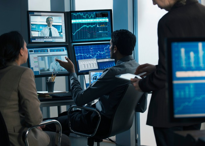 Three investment analysts watch screens on multiple monitors.