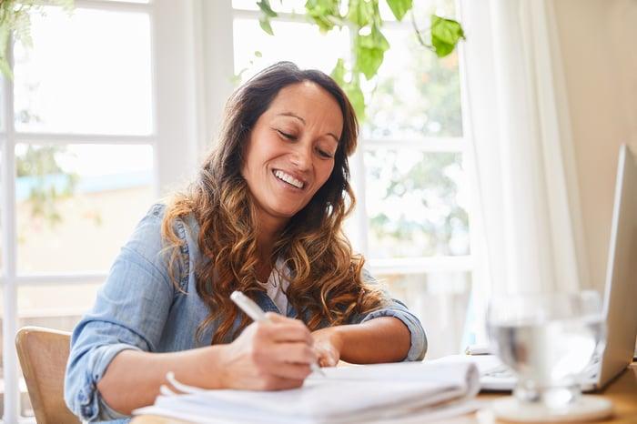 Femme, bureau, écriture, dans, cahier, et, sourire
