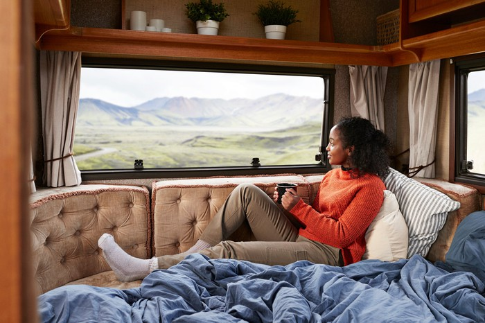 A woman looking at mountains from the window of her RV.