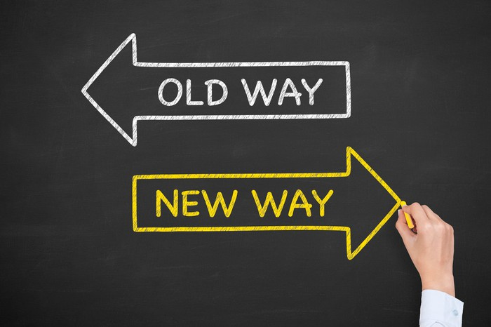 """A white arrow labeled """"old way"""" points left on a chalkboard. A yellow arrow labeled """"new way"""" points right."""