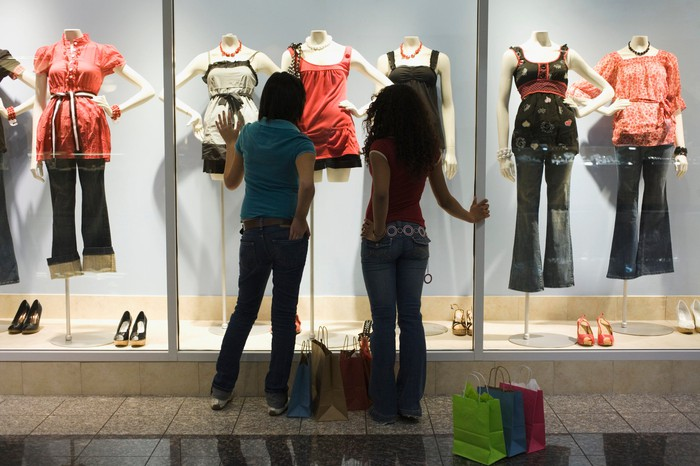 Two women stand facing a shopping mall windows with various mannequins on display.