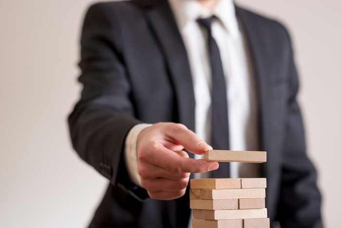 A business person strategically placing wooden blocks on a block tower.