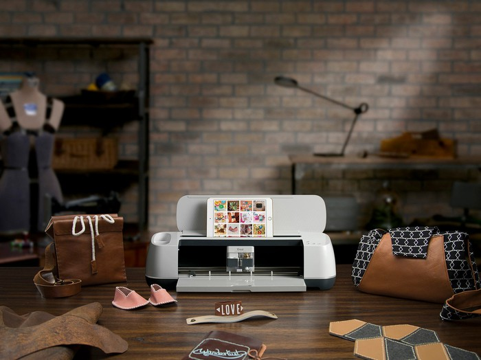 Cricut Maker surrounded by crafting supplies