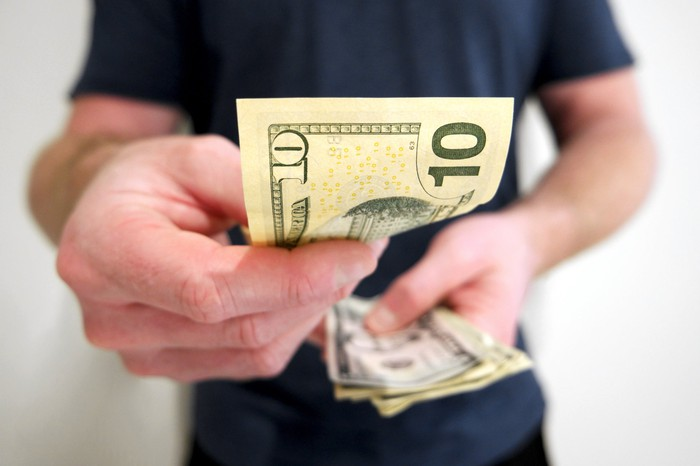 Man holding cash in his left hand presenting a $10 bill in his right hand.