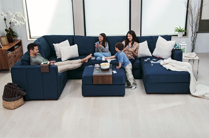 Family of four spread out on a giant blue couch from Lovesac.