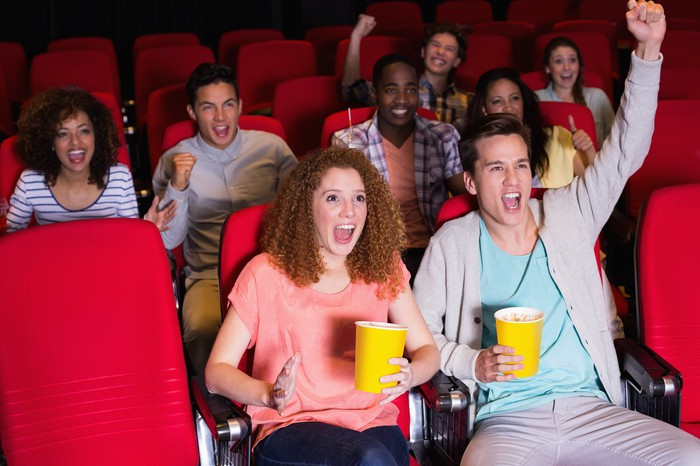 Small audience cheering in a movie theater