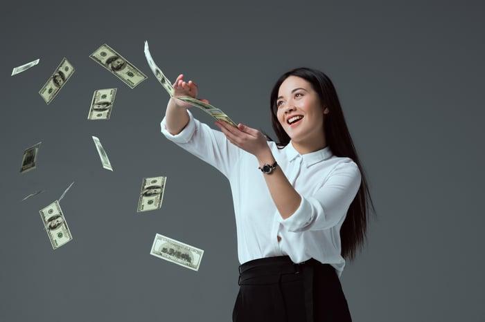 Smiling woman scattering $100 bills.