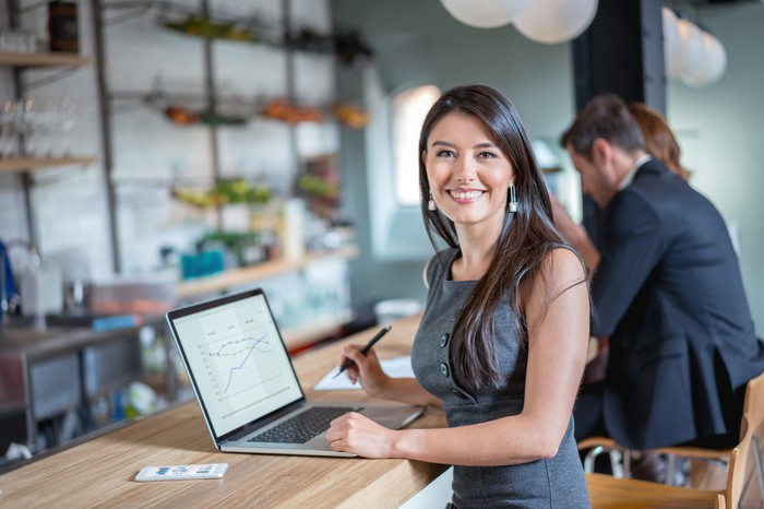 Young woman smiles while sitting at counter in front of laptop and cell phone.