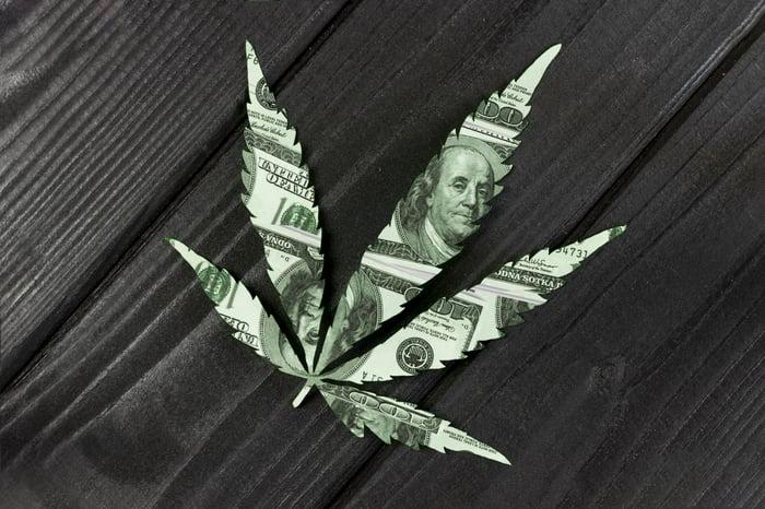 Dollar bills are cut into the shape of a cannabis leaf.