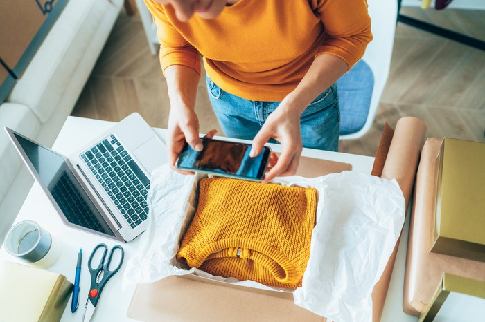 A person takes a photo of a yellow sweater folded into a box for shipping