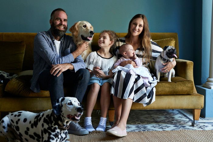 a family sitting on a couch with three dogs