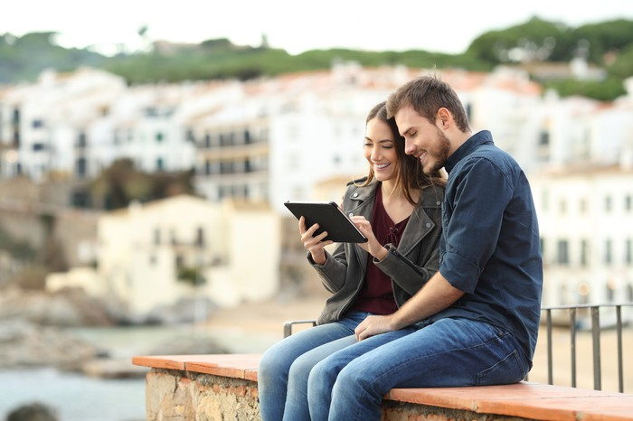 A couple watches a video on a tablet outside