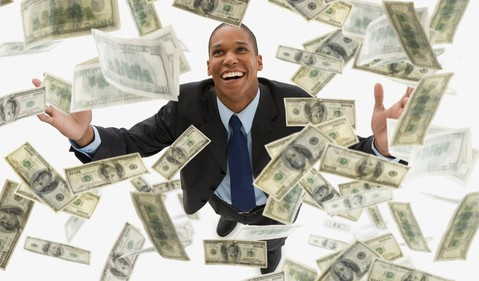 Smiling man in suit raising arms as hundred-dollar bills float above and around him_GettyImages-83520698
