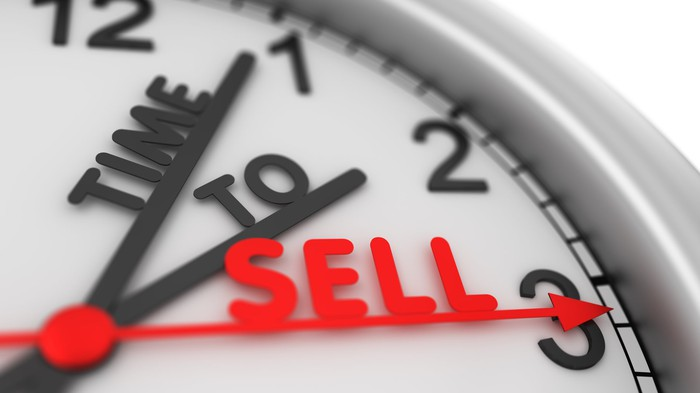 Clock face with hands spelling out the words time to sell.