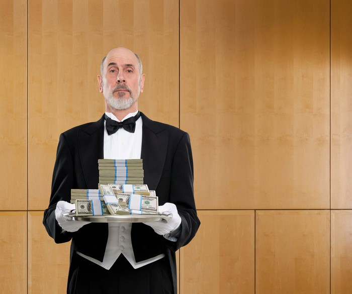 A butler in a tux is holding a platter filled with money.