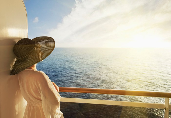 Woman in large hat standing on a cruise ship deck, looking out to sea.