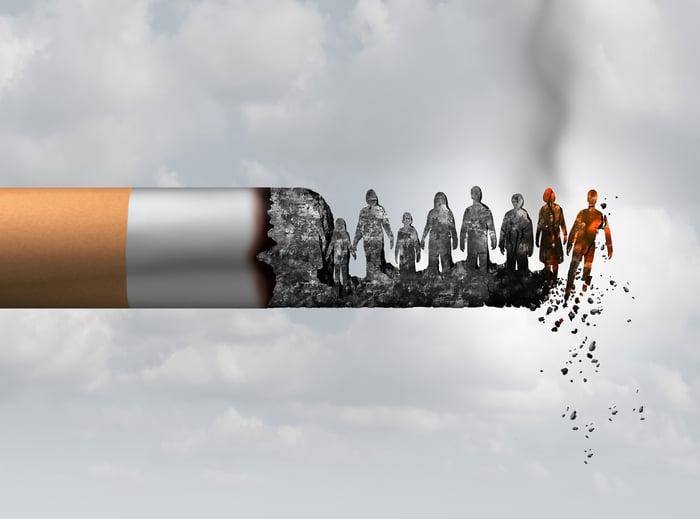 Une cigarette allumée avec des cendres en forme de personnes.
