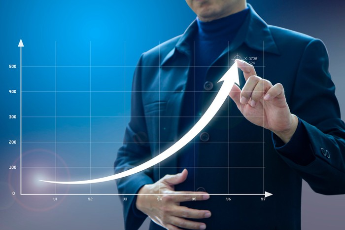 A businessman draws an exponential growth curve on a line graph.