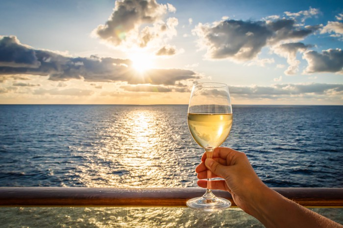 A person is holding a wine glass up to the sky while onboard a cruise ship.