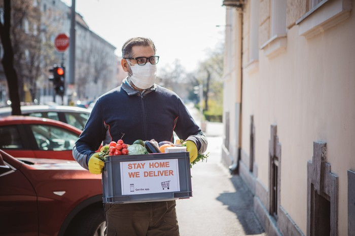 man with mask and gloves delivering box of food in city