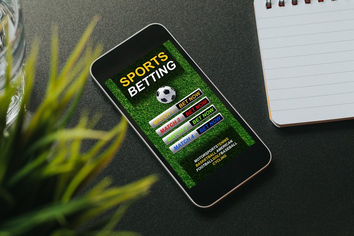 A smartphone with a sports betting app on its screen resting on a desktop between a notepad and a potted plant.